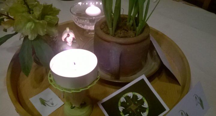 Autel d'Imbolc avec deux bougies, un pot de Perce-neige et des Hellébores