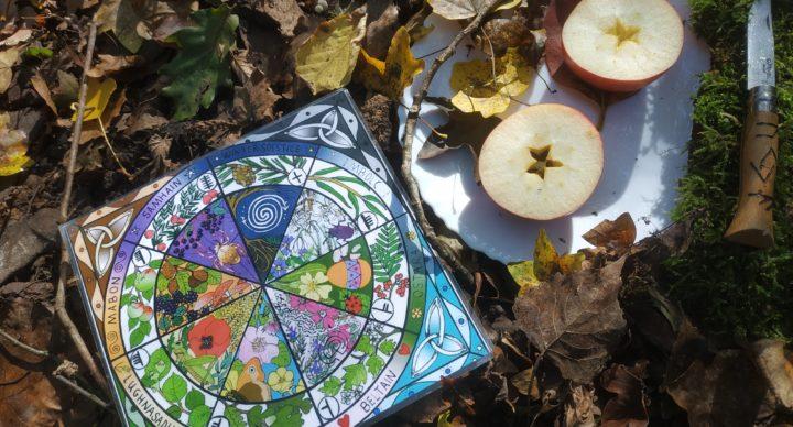 Autel de Samhain comprenant une roue des saisons, une pomme coupée en deux montrant le pentacle contenant les graines. Le tout sur un sol de feuilles d'automne.